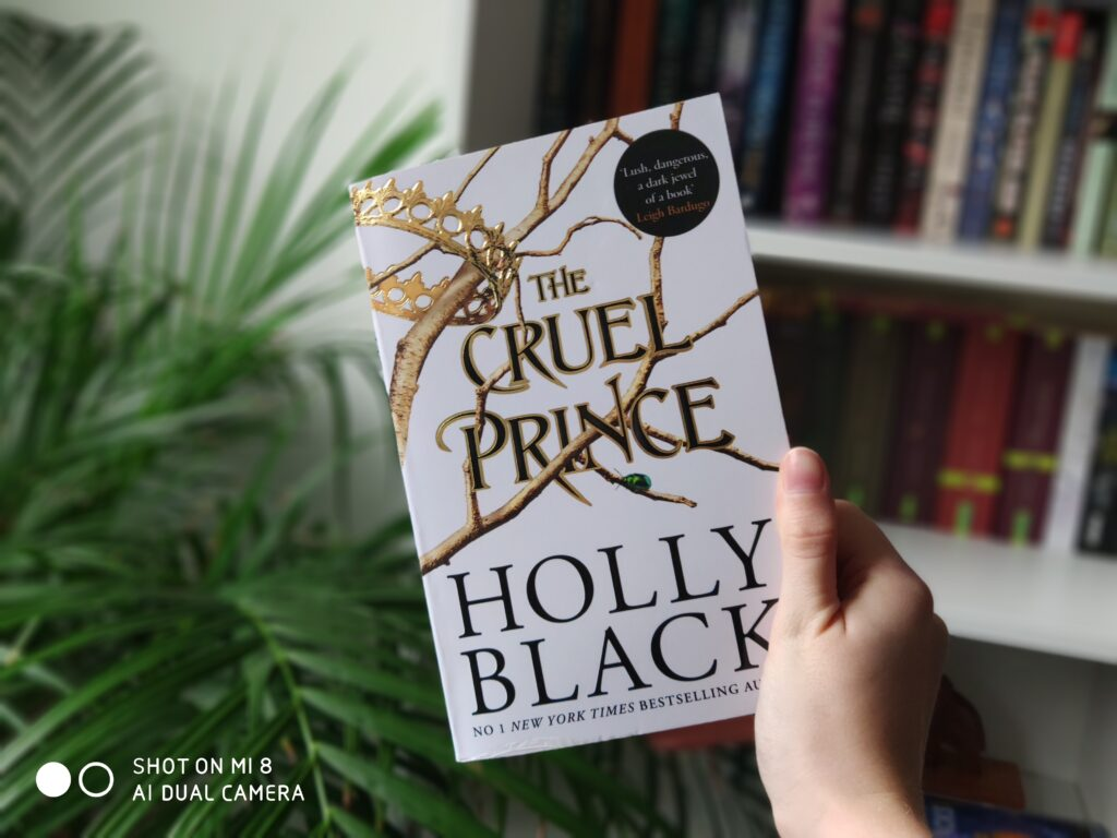 """Das Buch """"The Cruel Prince"""" in einer Hand vor einer Pflanze und einem Bücherregal."""