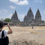 Eine Frau fotografiert die Prambanan Tempelanlage in Indonesien.