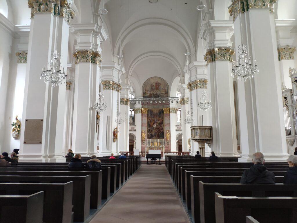 Ein weißer Innenraum mit schwarzen Holzbänken und durchsichtien Kronleuchter der Jesuitenkriche in Heidelberg.