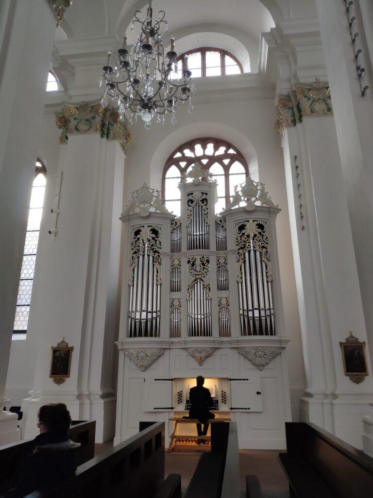 Ein Orgler sitzt an einer weißen Orgel und spielt Musik in der Jesuitenkirche in Heidelberg.