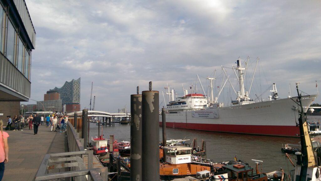 Der Hamburger Hafen mit der Elbphilharmonie im Hintergrund und Schiffen auf dem Meer.