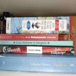 Mehrere Bücher übers Reisen liegen auf einem Stapel.
