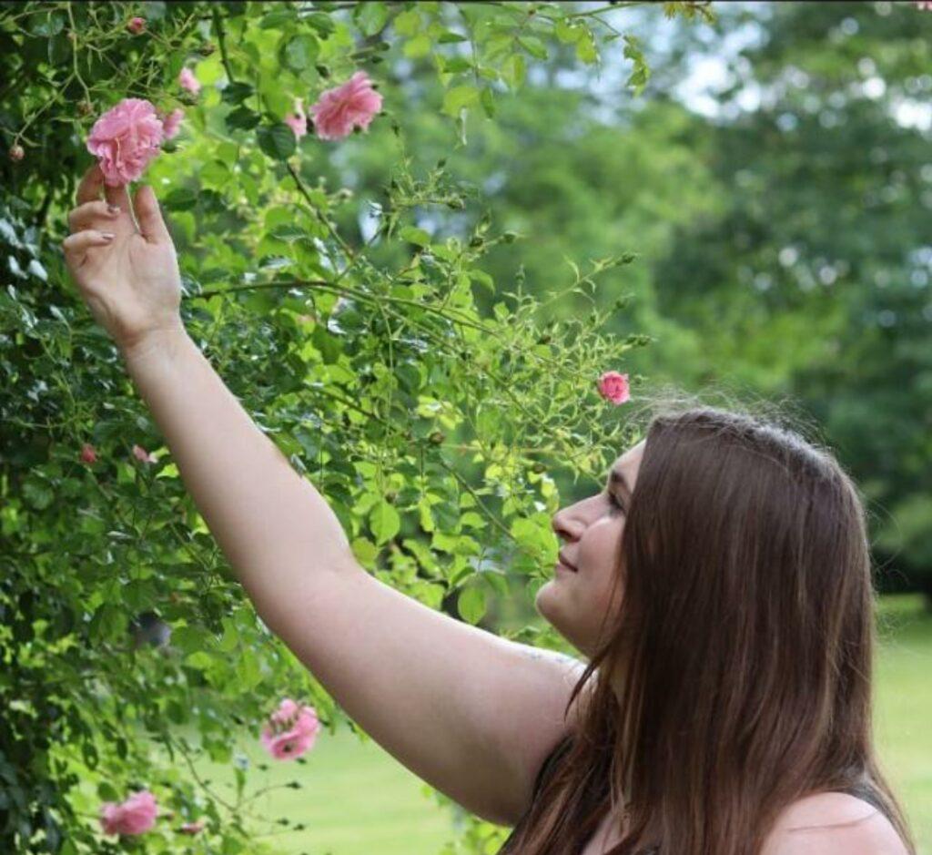 Juliane vor einem Rosenstrauß