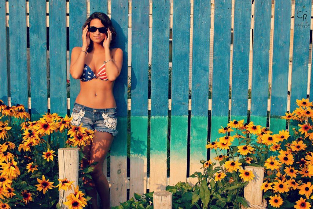 Frau mit Sonnenbrille, Bikini-Oberteil und Hotpans vor einem blauen Zaun mit gelben Blumen.