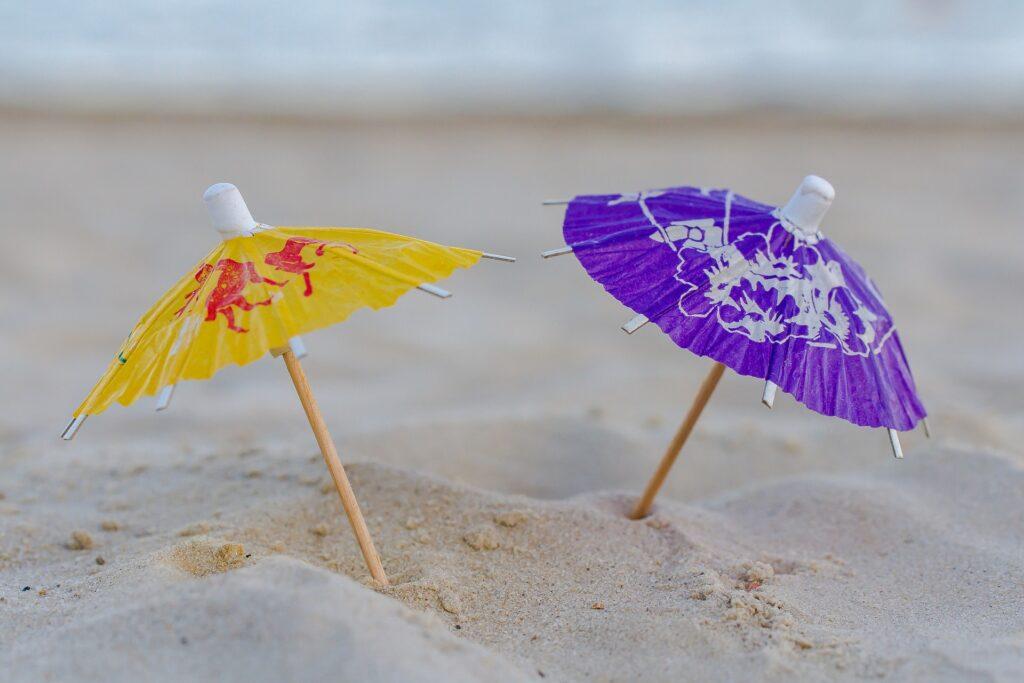 Zwei kleine Sonnenschirme im Sand