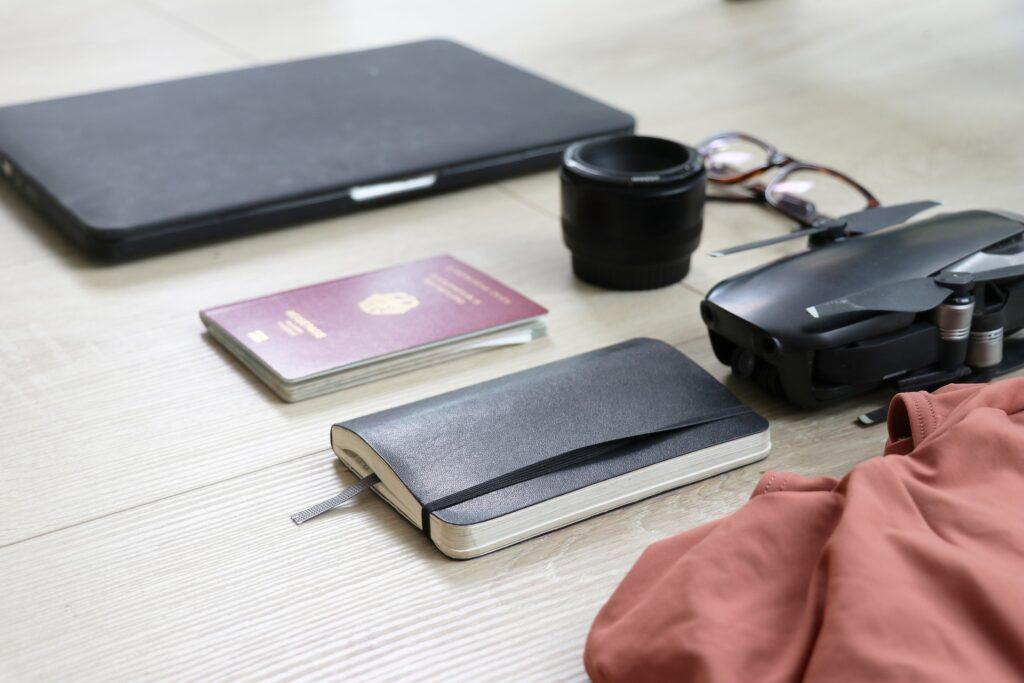 Drohne, Laptop, Notizbuch und Reisepass auf einem Tisch