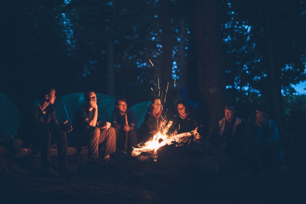 Junge Leute sitzen nachts vor einem Lagerfeuer.