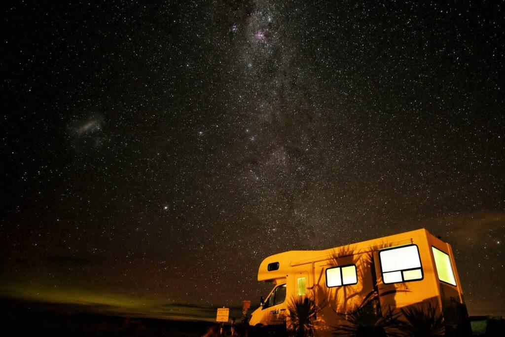 Ein Wohnmobil in der Nacht unter einem Sternenhimmel.