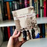 Das Buch Nanking Road von Anne C. Veerhoeve vor einem Bücherregal.