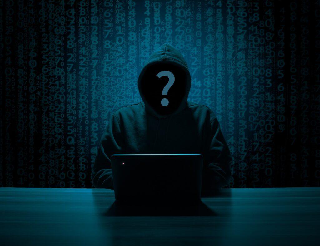 Eine dunkle Gestalt mit Kaputzenpullover sitzt vor einem Laptop.